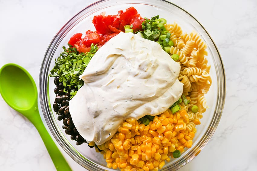 creamy sauce on top of taco pasta salad ingredients in a mixing bowl