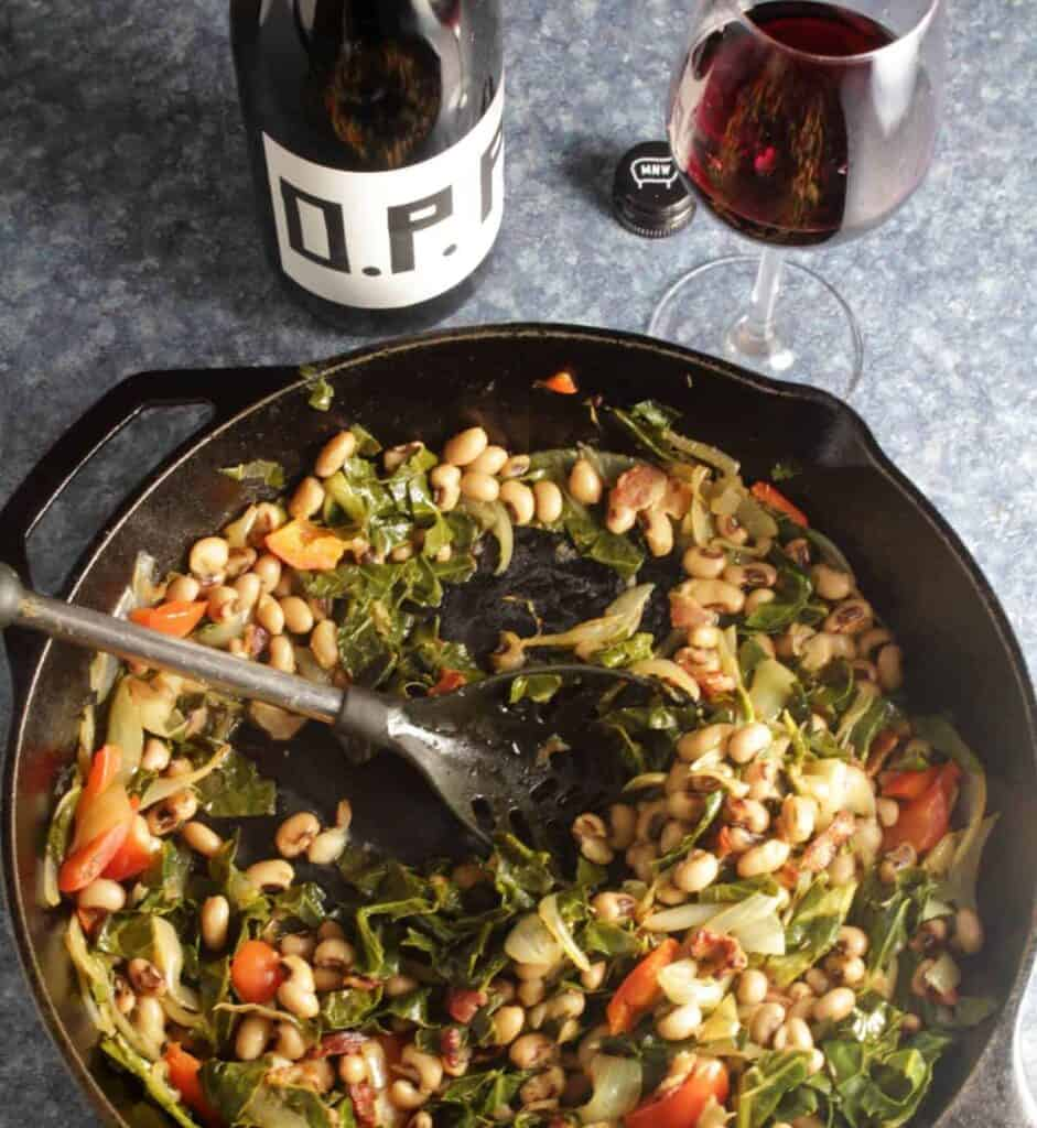 serving spoon in a cast iron pan of black-eyed peas with collard greens sitting next to a glass of wine