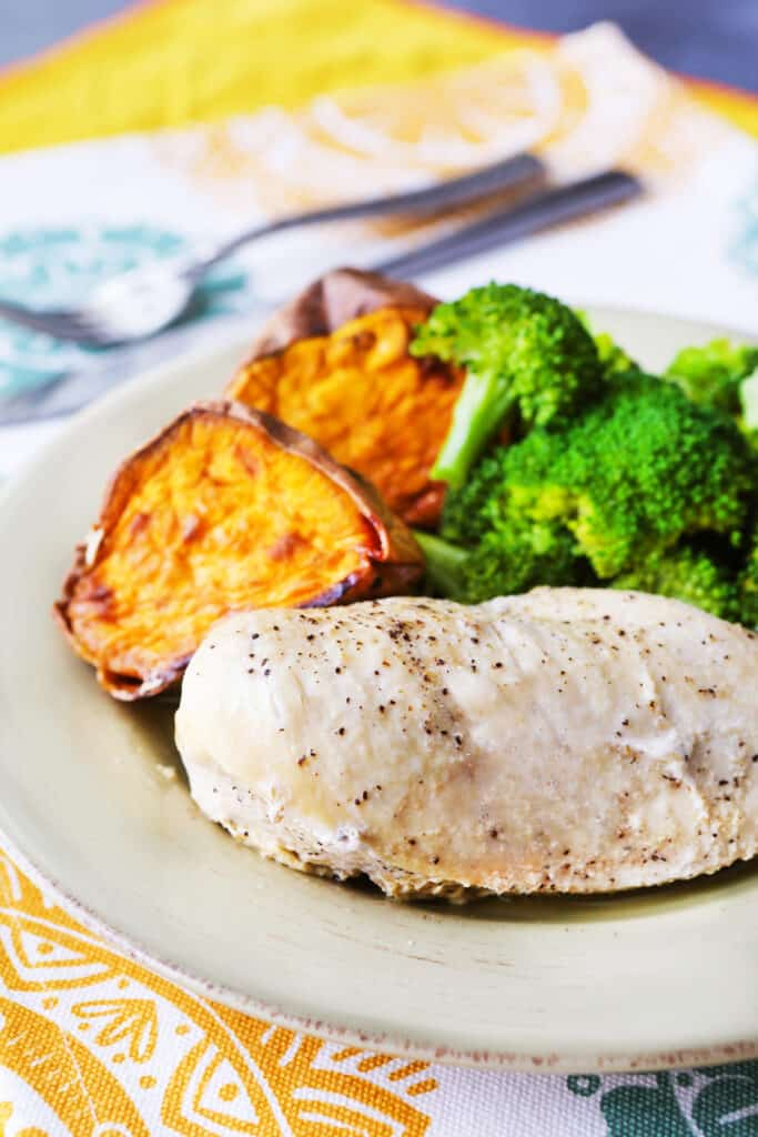 Grilled chicken on a plate with two halves of a sweet potato and broccoli alongside it.