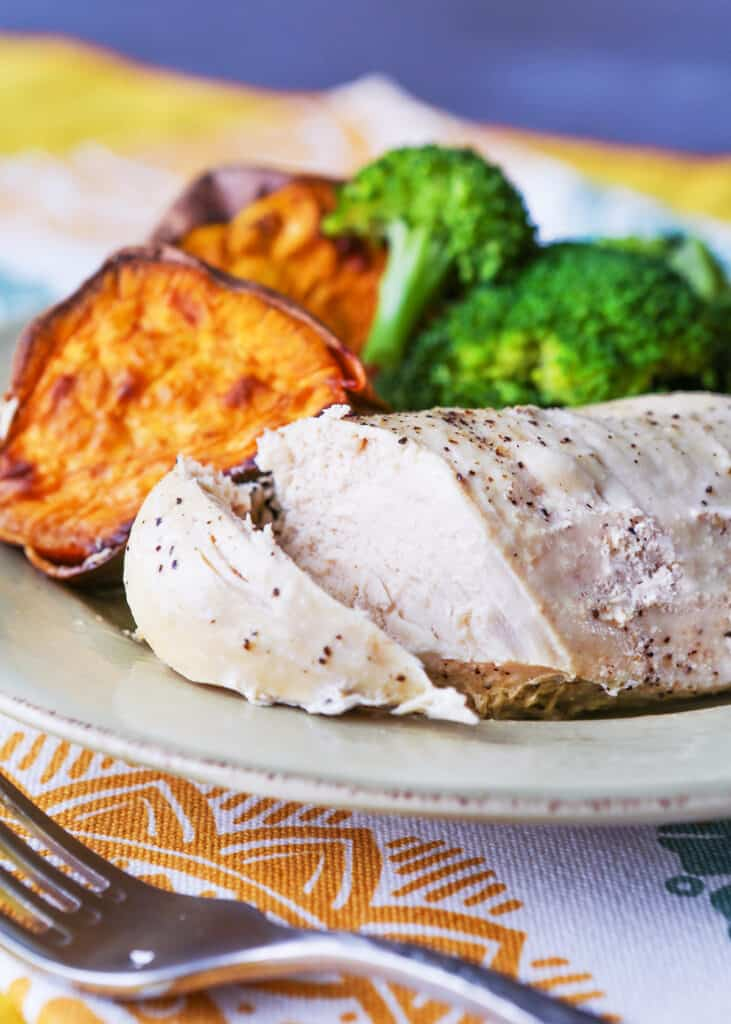 Instant pot grilled chicken cut open so you can see the juicy piece on a plate next to cooked sweet potatoes and broccoli.