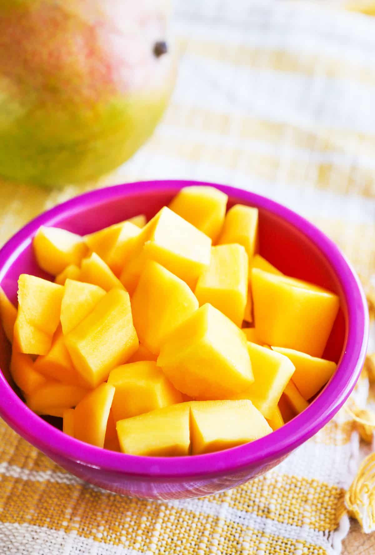 Bowl of mango pieces sitting next to a mango