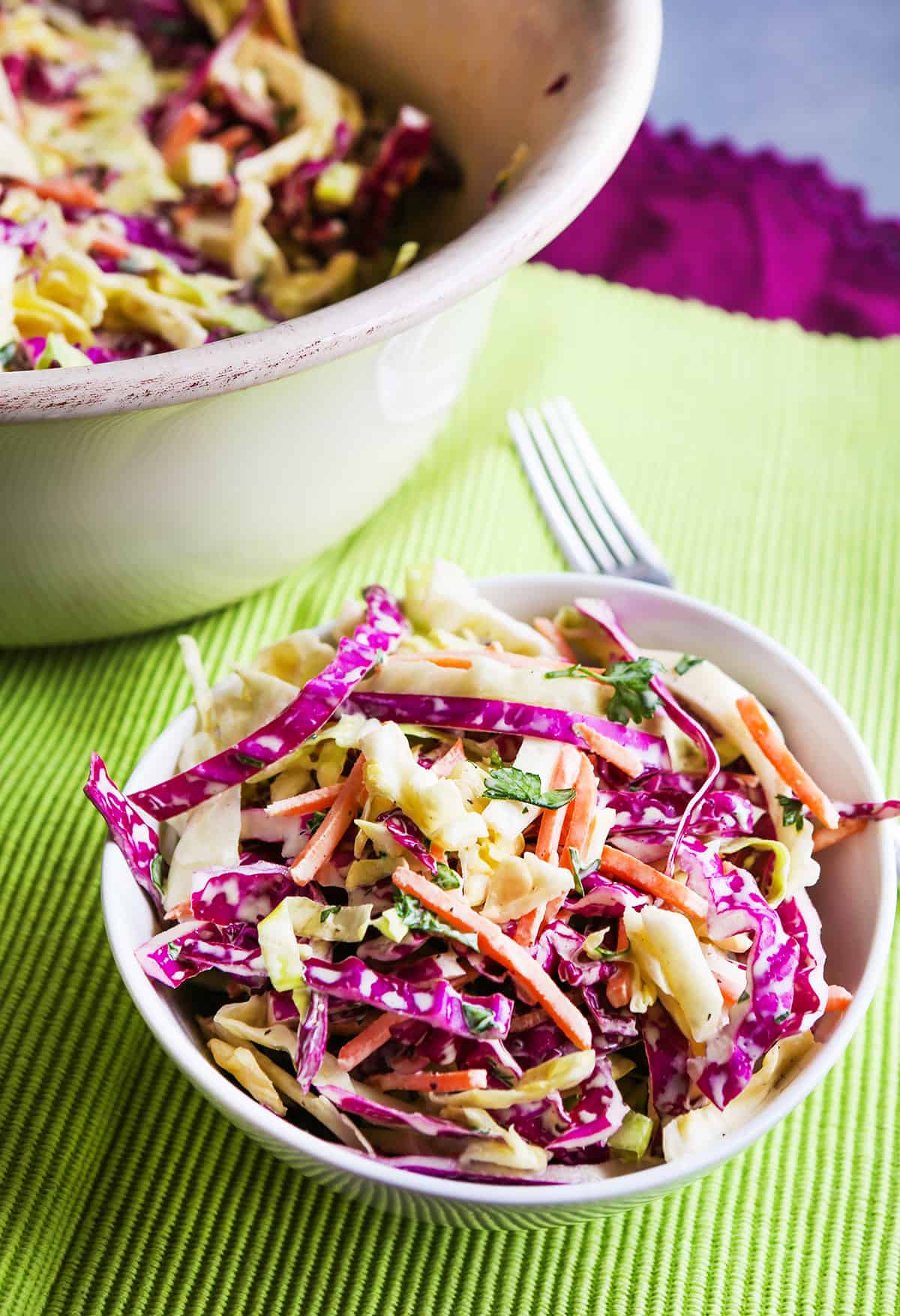 Serving of coleslaw in a bowl sitting next to mixing bowl.