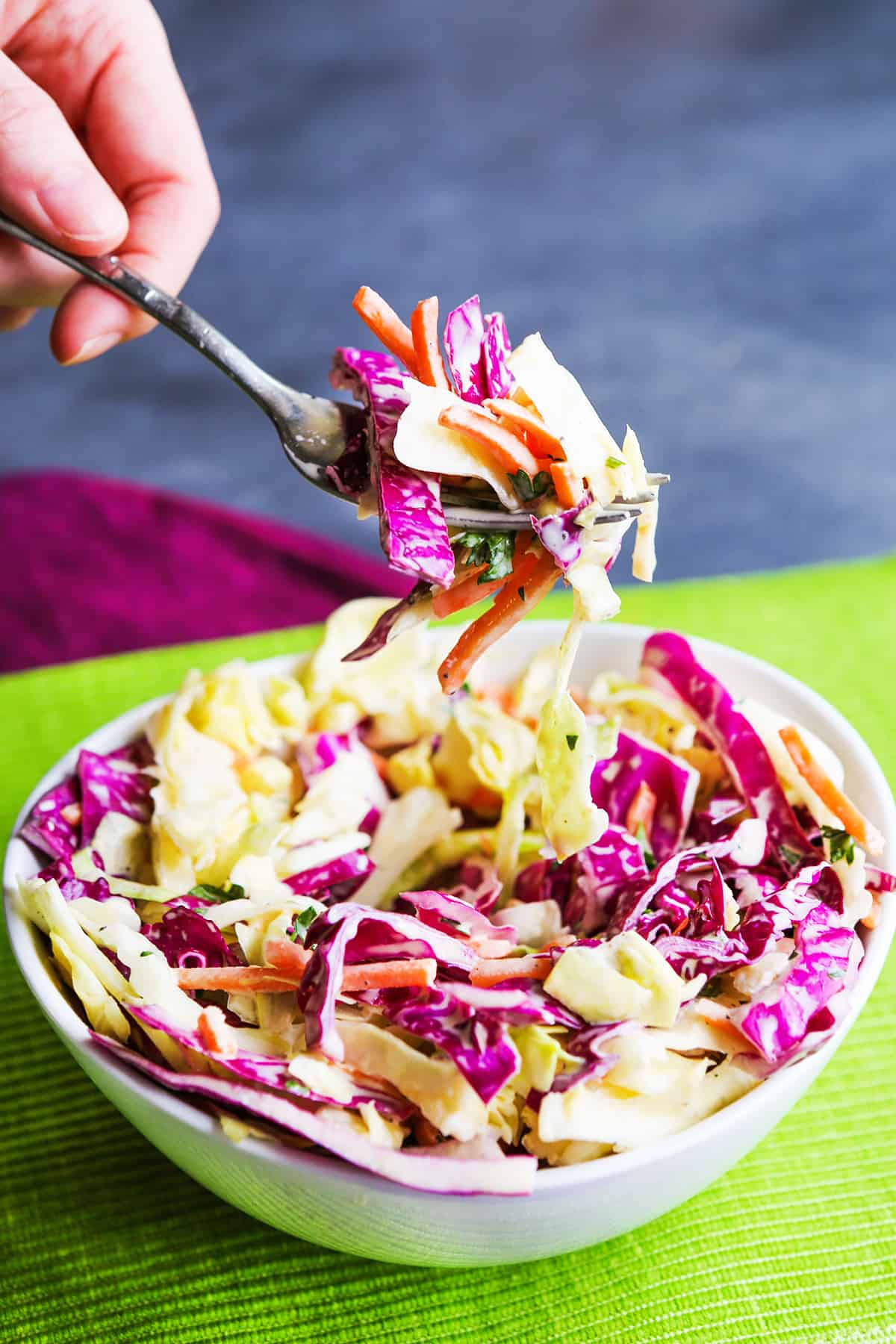 Fork pulling a bite of coleslaw out of a bowl.
