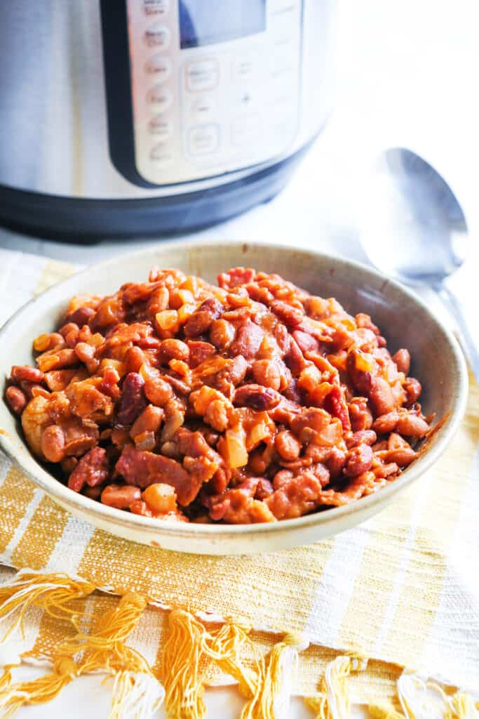 Bowl of baked beans ready to serve sitting next to an Instant pot.