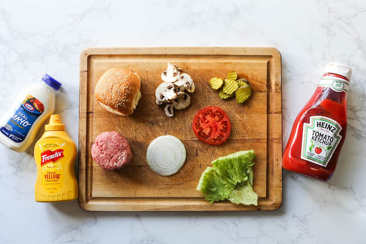 Five guys burger ingredients on a cutting board.