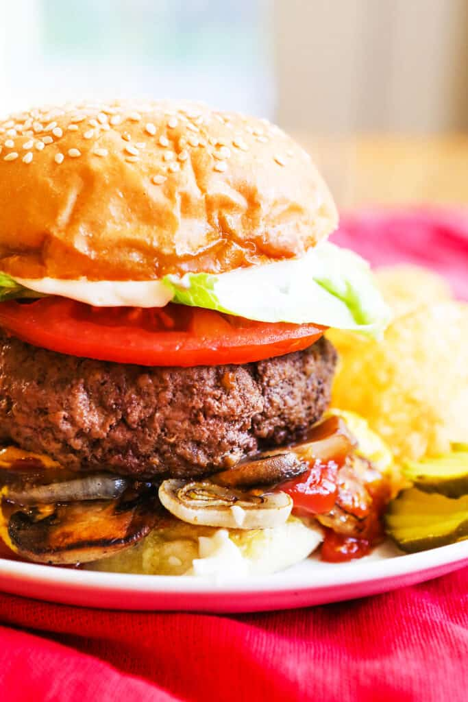 A five guys burger  topped with tomatoes, lettuce, onions and mushrooms and pickles sitting next to it on a plate.