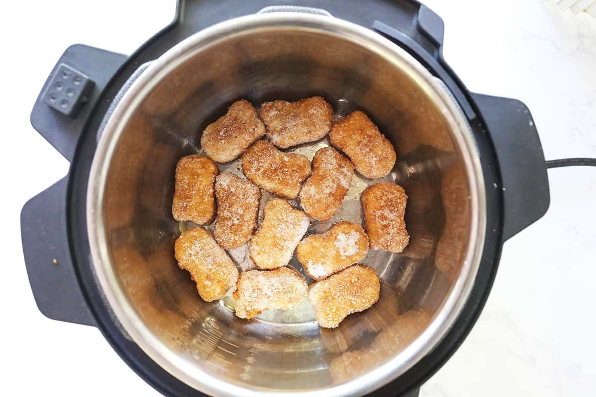 Frozen chicken nuggets in a single layer inside an air fryer.