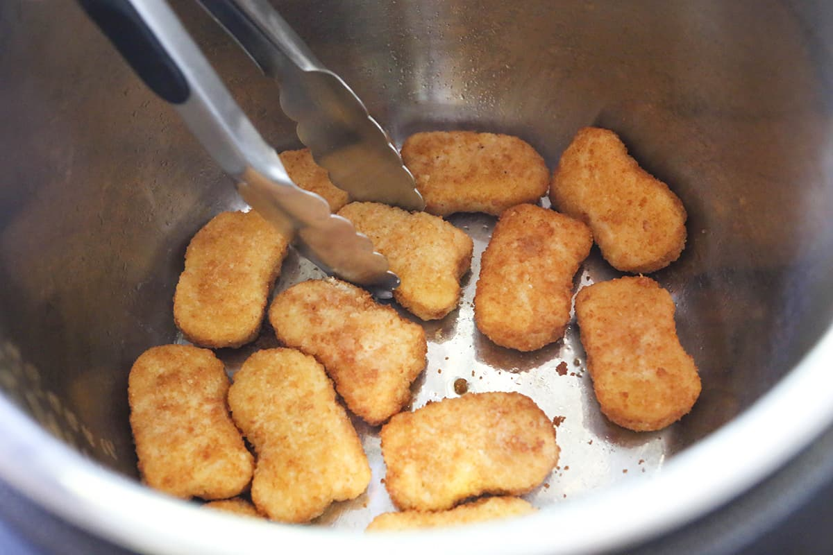 Pair of tongs flipping nuggets in an air fryer.