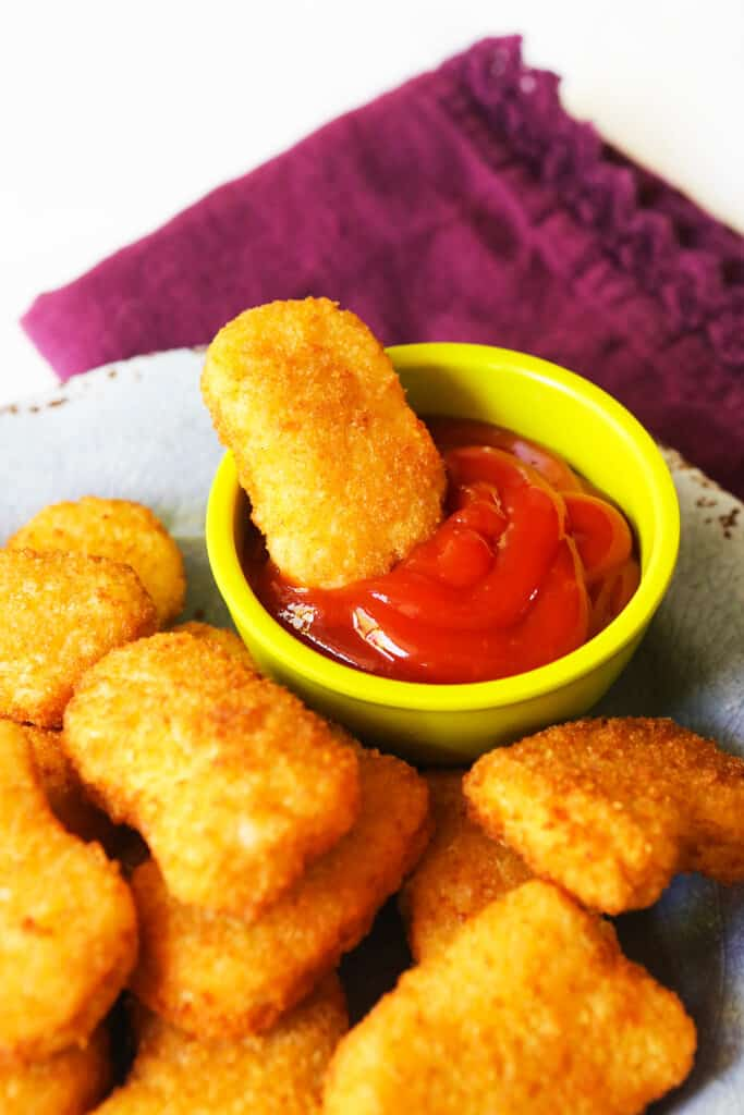 Air fried chicken nuggets on a plate with a bowl of ketchup that has a nugget sitting in it.