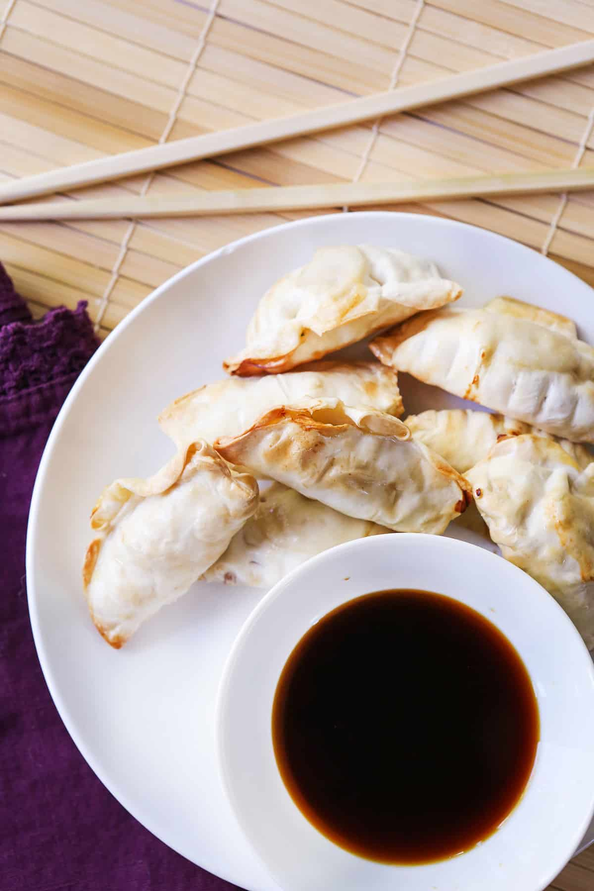 Top view of dumplings on a plate sitting next to chopsticks and soy sauce.