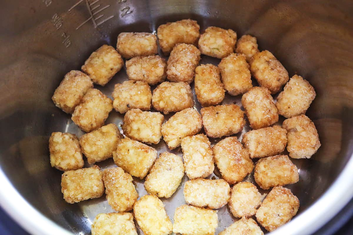 Frozen tater tots lined up in a single layer inside an air fryer.