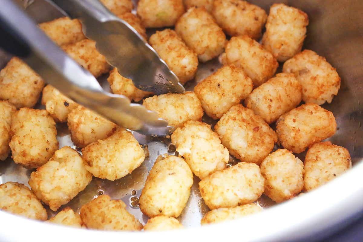 Tongs flipping tater tots over in an air fryer.
