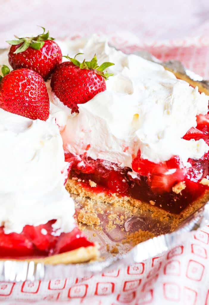 No bake strawberry pie topped with whipped cream and fresh strawberries.