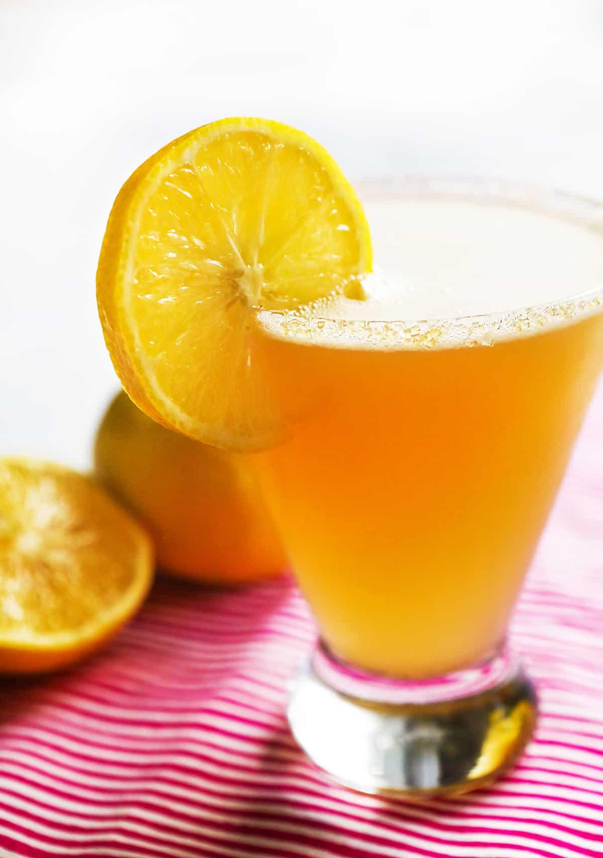 Close up of a lemon drop cocktail next to lemons.
