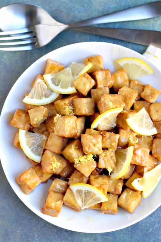 air fryer lemon tofu with quarter slices of lemon on a plate
