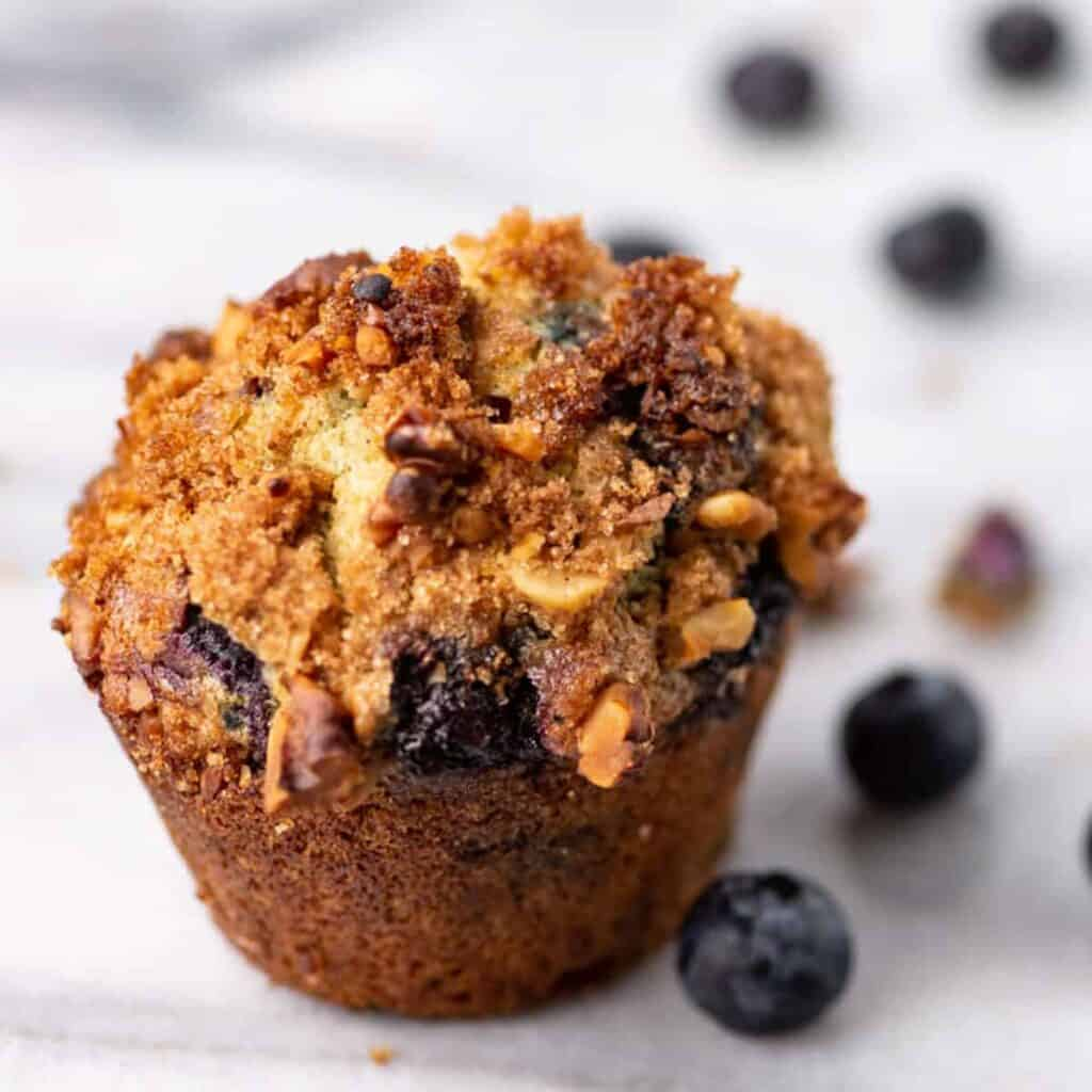single blueberry muffin sitting on counter next to fresh blueberries