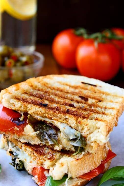 caprese panini sandwich cut in half on a plate