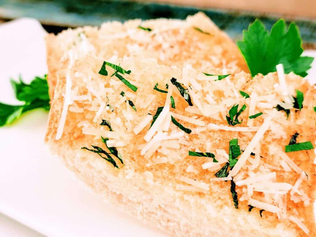 slice of garlic bread and parsley sprinkled on top
