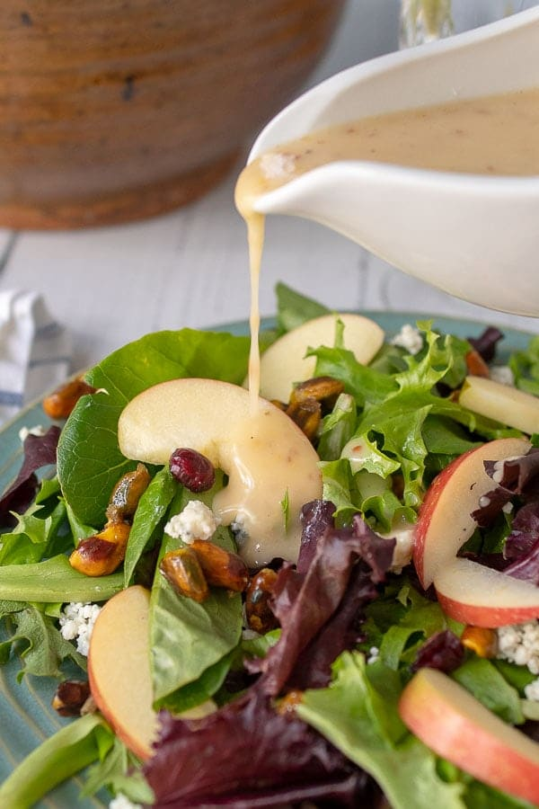 plate of harvest salad with dressing being drizzled over it