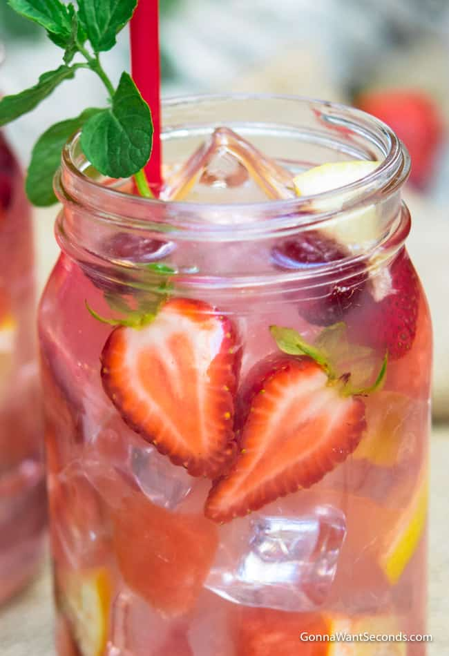 hippie juice in a mason jar with slices of fresh fruit and a herb garnish