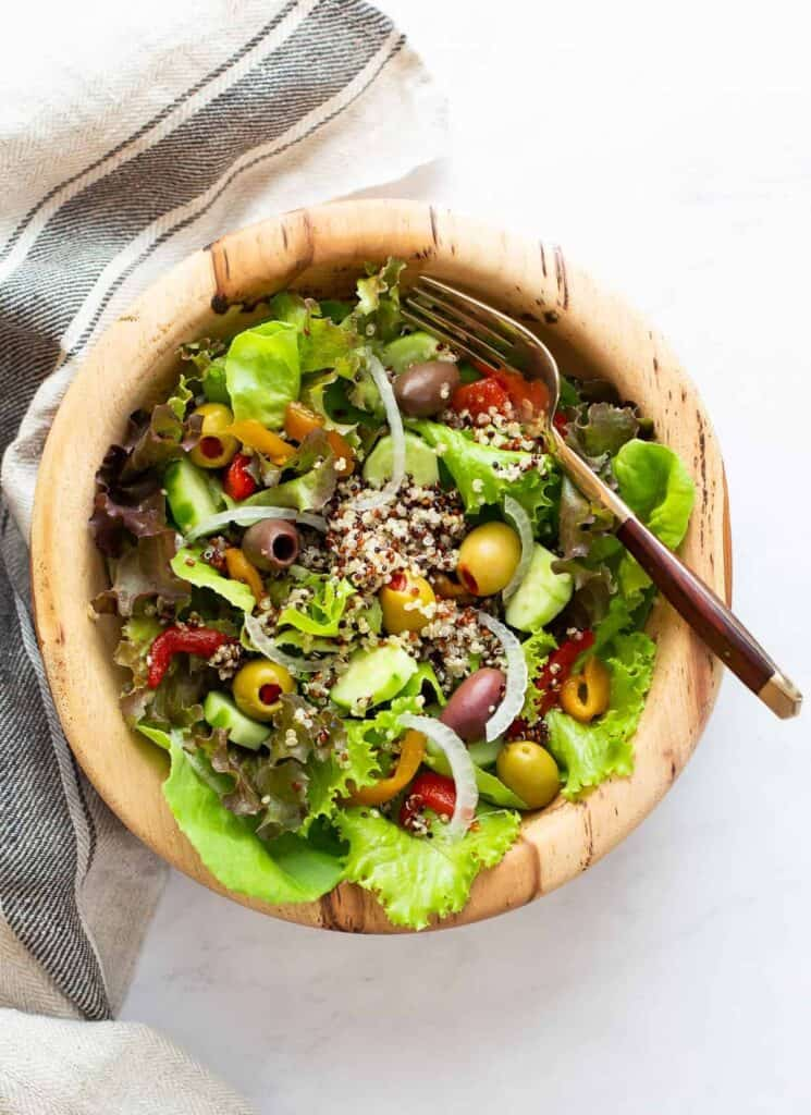 top view of leafy green salad topped with quinoa and olives