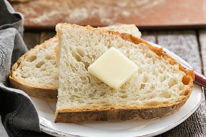 two slices of no knead bread on a small plate and a pat of butter on top