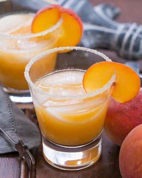 fresh peach margaritas with a sugar rim around the glass and a peach slice garnish