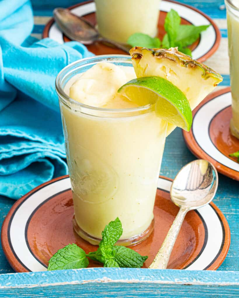 non alcoholic pina colada with lime and pineapple garnishes