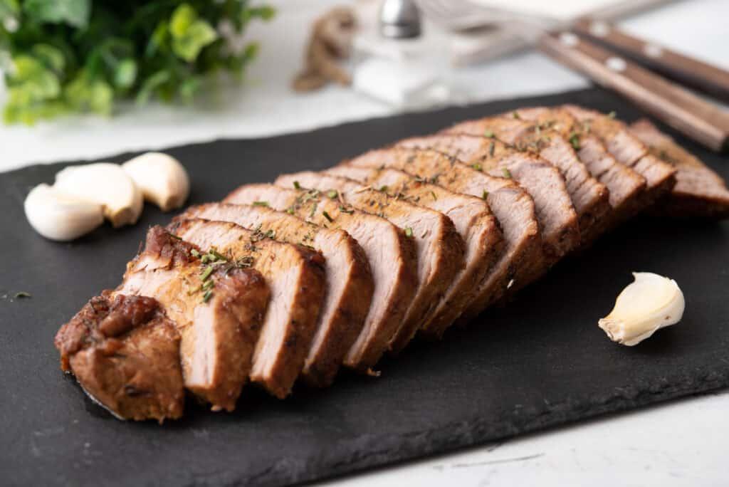 sliced instant pot roast beef on a cutting board and whole garlic garnish alongside