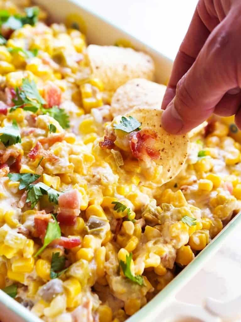 hand scooping slow cooker hot corn dip onto a chip