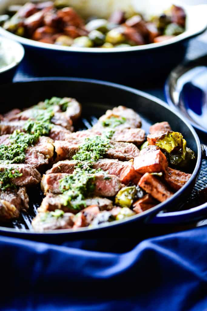 strip loin with veggies cooking in a cast iron pan with chimichurri sauce drizzled on top