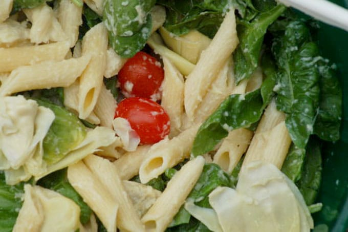 pasta mixes with cherry tomatoes and spinach