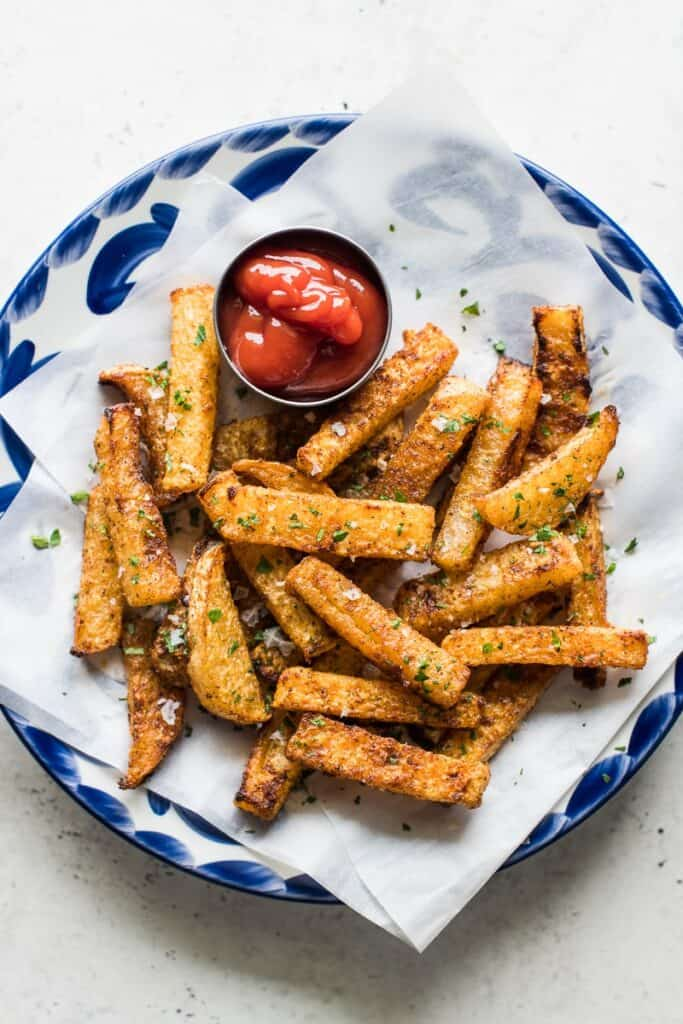 baked jicama fries on a plate with a saucer of ketchup
