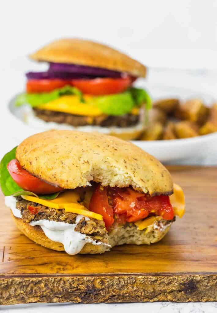 black bean quinoa burger sitting on a board with a bite out of it and sauce dripping out