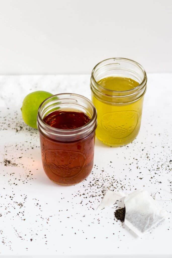 two mason jars with cold brew tea next to a lime and open tea bag on the table