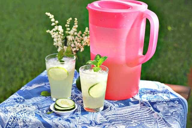 cucumber lime agua fresca in a pitchen sitting next to two glasses filled and a lime garnish