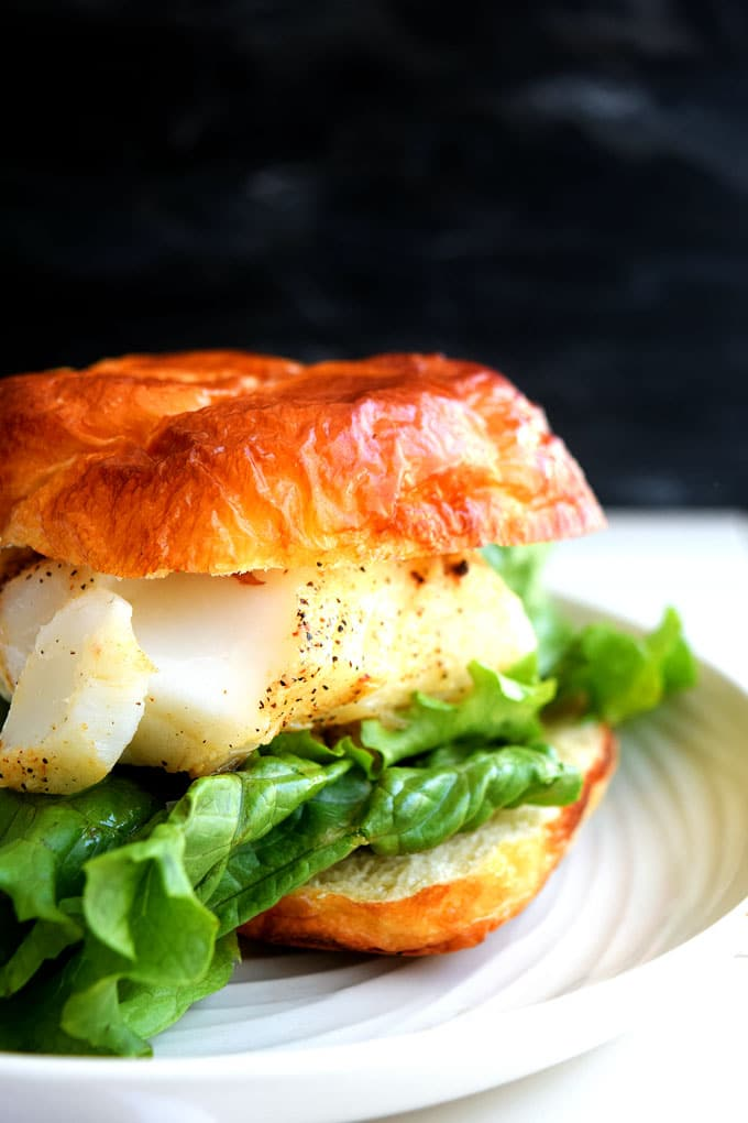 a plate with a cod croissant with lettuce sandwich