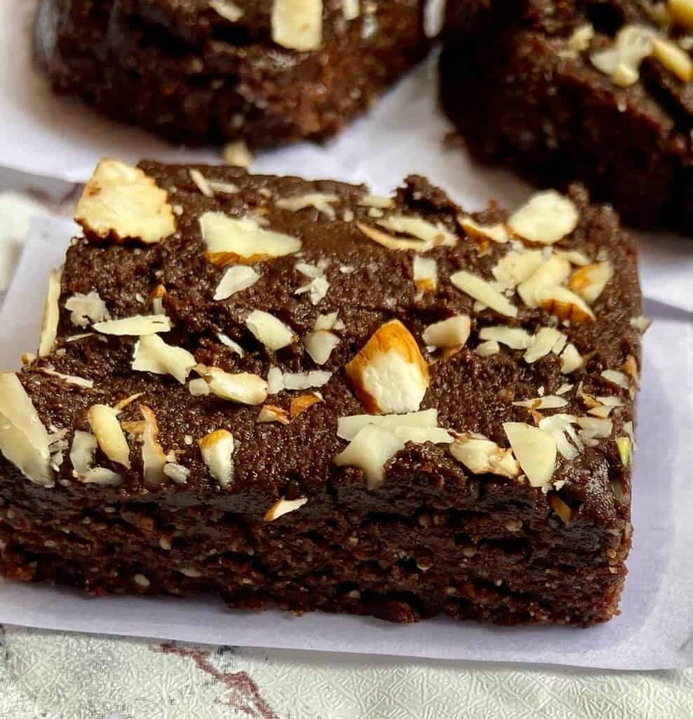 a single slice of no bake brownies with chopped almonds over it sitting on a napkin.