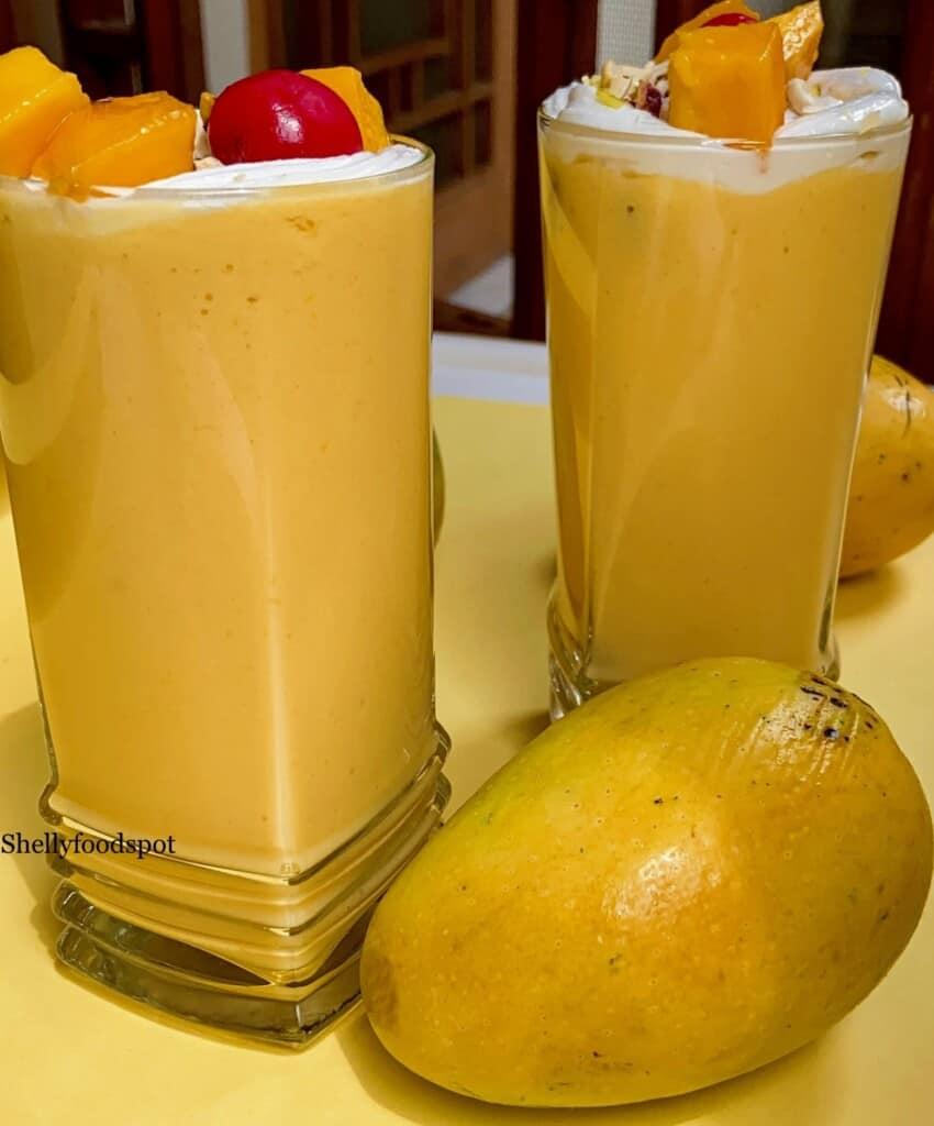 two glasses of mango milkshake wiht a mango garnish and a whole mango sitting in front