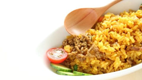 rice in a serving bowl with a wooden spoon alongside
