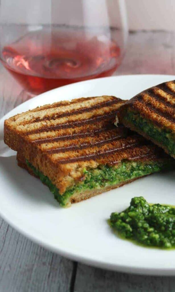 a kale pesto grilled cheese sandwich with grill marks on top cut in half sitting on a plate next to a glass of wine