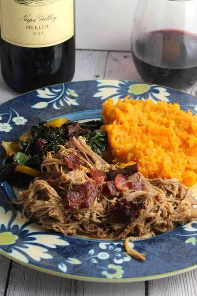 pulled pork with bacon shredded on  a plate with a mashed sweet potato on the side and a glass of wine off to the side