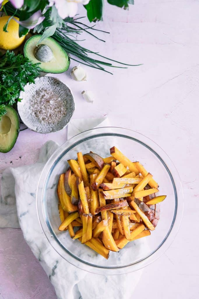 glass bowl of roasted beet fries next to cut open avocados