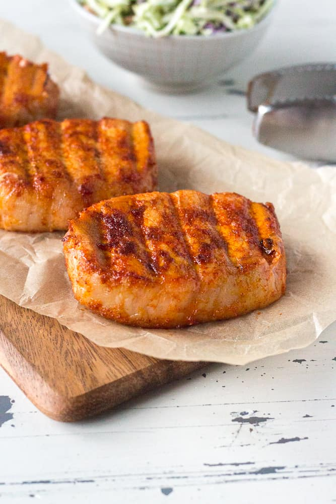 smoked boneless pork chops sitting on a piece of wax paper seasoned and cooked, ready to serve
