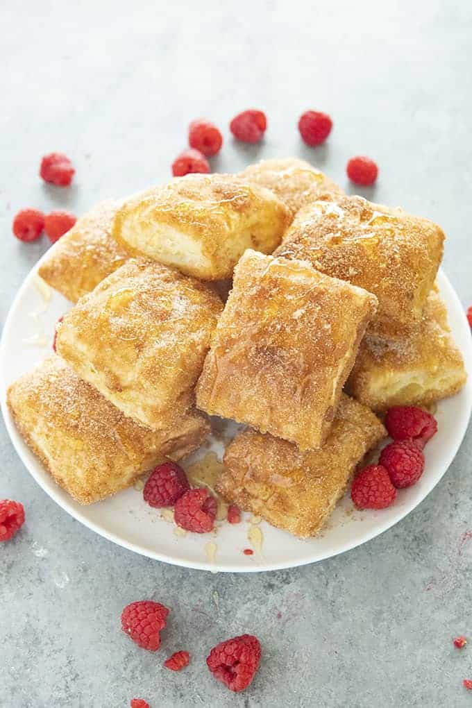 heaping plate of baked sopapillas and fresh raspberries strewn around