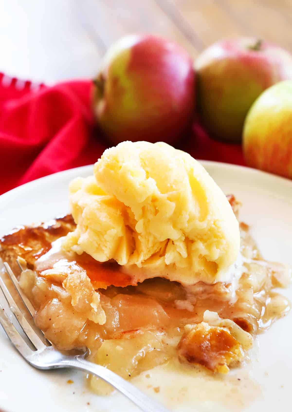 Piece of easy apple pie with bite take out and vanilla ice cream on top.