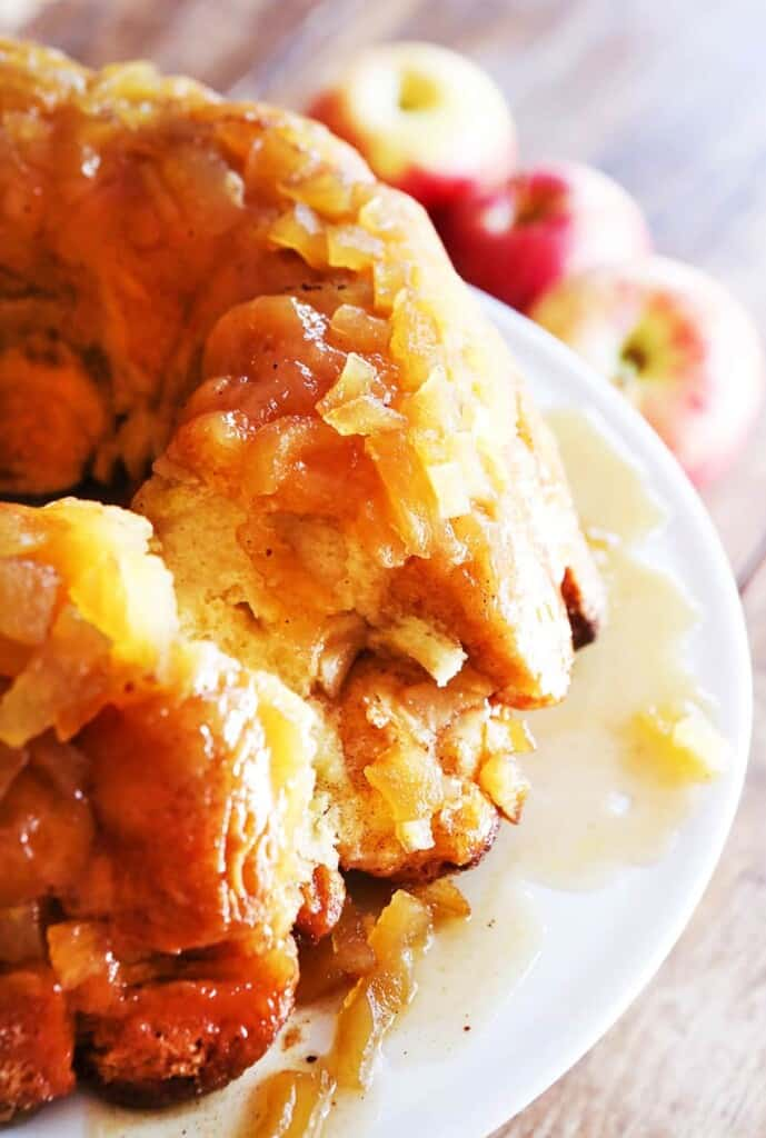 Side view of bundt monkey bread with apples on a plate with a few pieces removed.