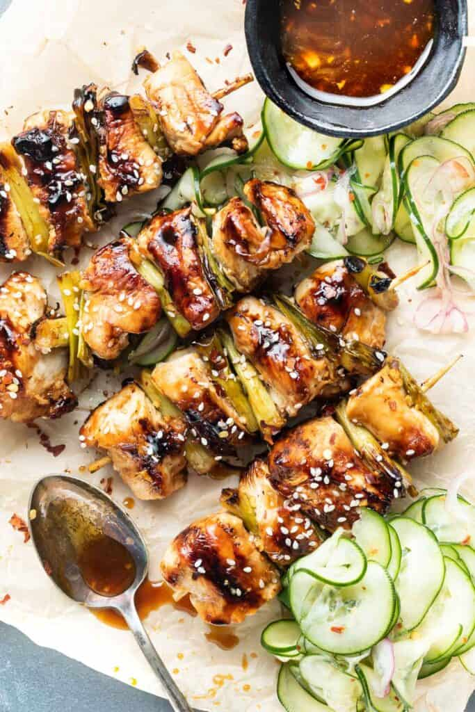 Chicken teriyaki skewers on a platter with a spoon with leftover sauce that was drizzled over the chicken and pickled cucumbers on the side.