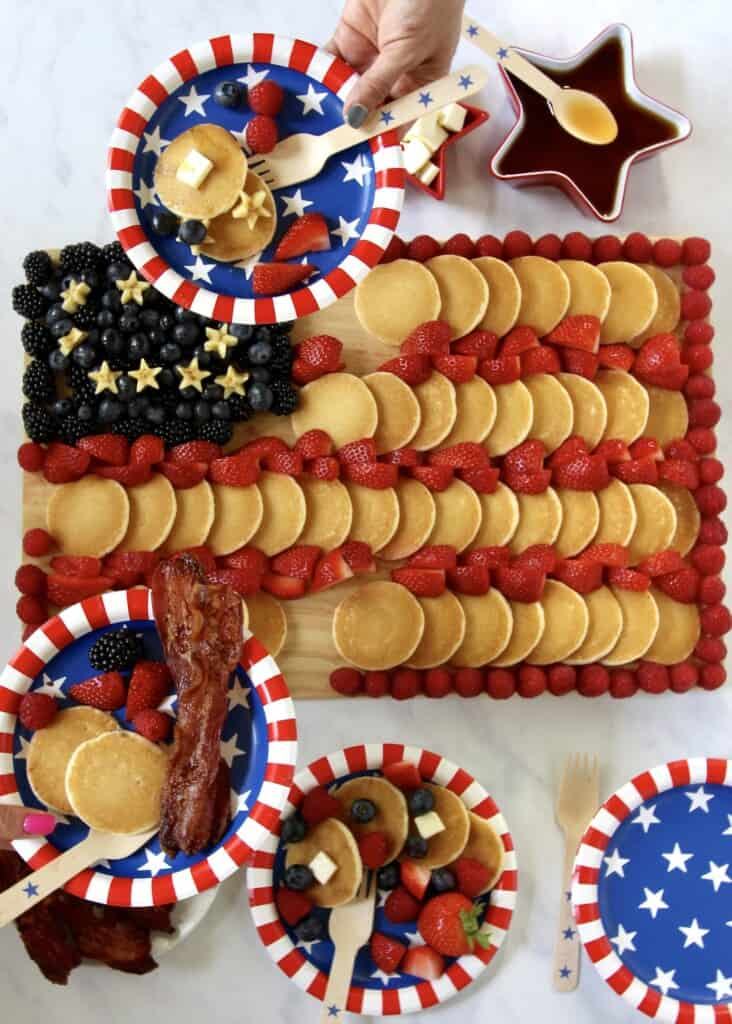 A paper plate full of food from a cutting board filled with mini pancakes and fruit decorated as the American flag.
