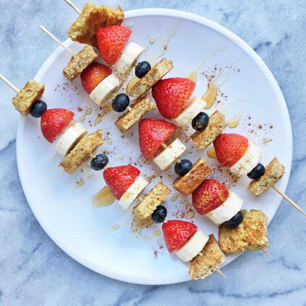 3 Patriotic French Toast Skewers laid across a plate with maple syrup drizzle over them.
